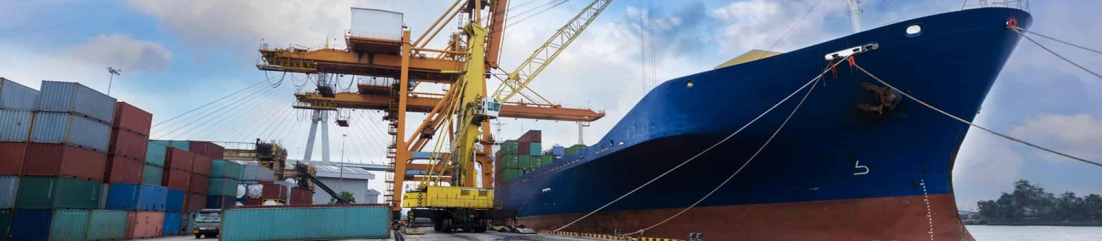 Industrial Container Cargo freight ship with working crane bridge in shipyard with truck